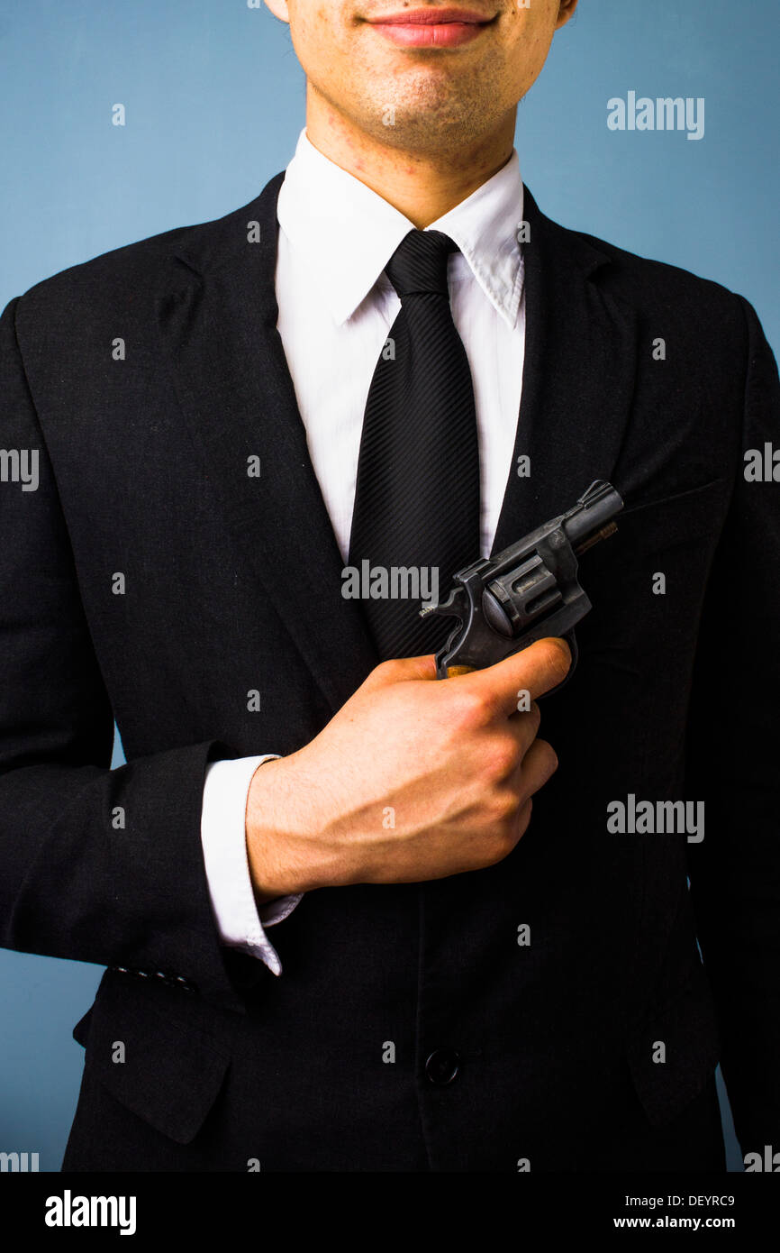 Young man in suit is holding a gun - Stock Image