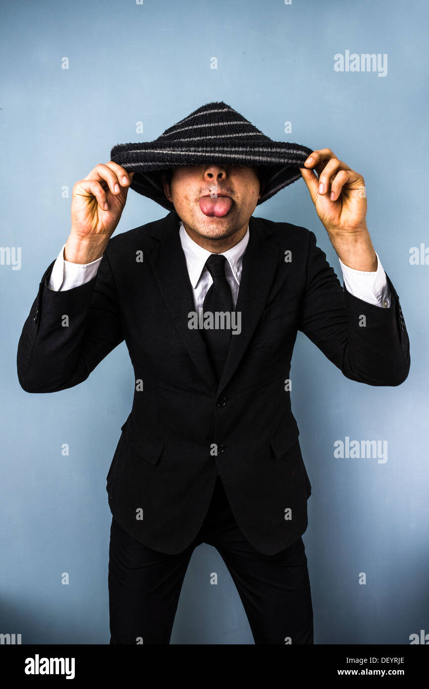 Silly businessman is hiding under his woolen hat and blowing a raspberry - Stock Image