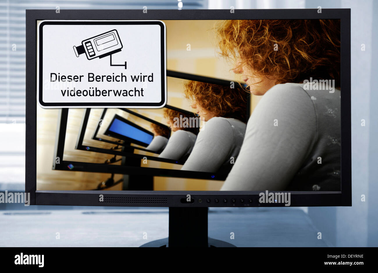 Woman at the computer with sign 'Dieser Bereich wird videoueberwacht', German for 'this area is under video surveillance' - Stock Image