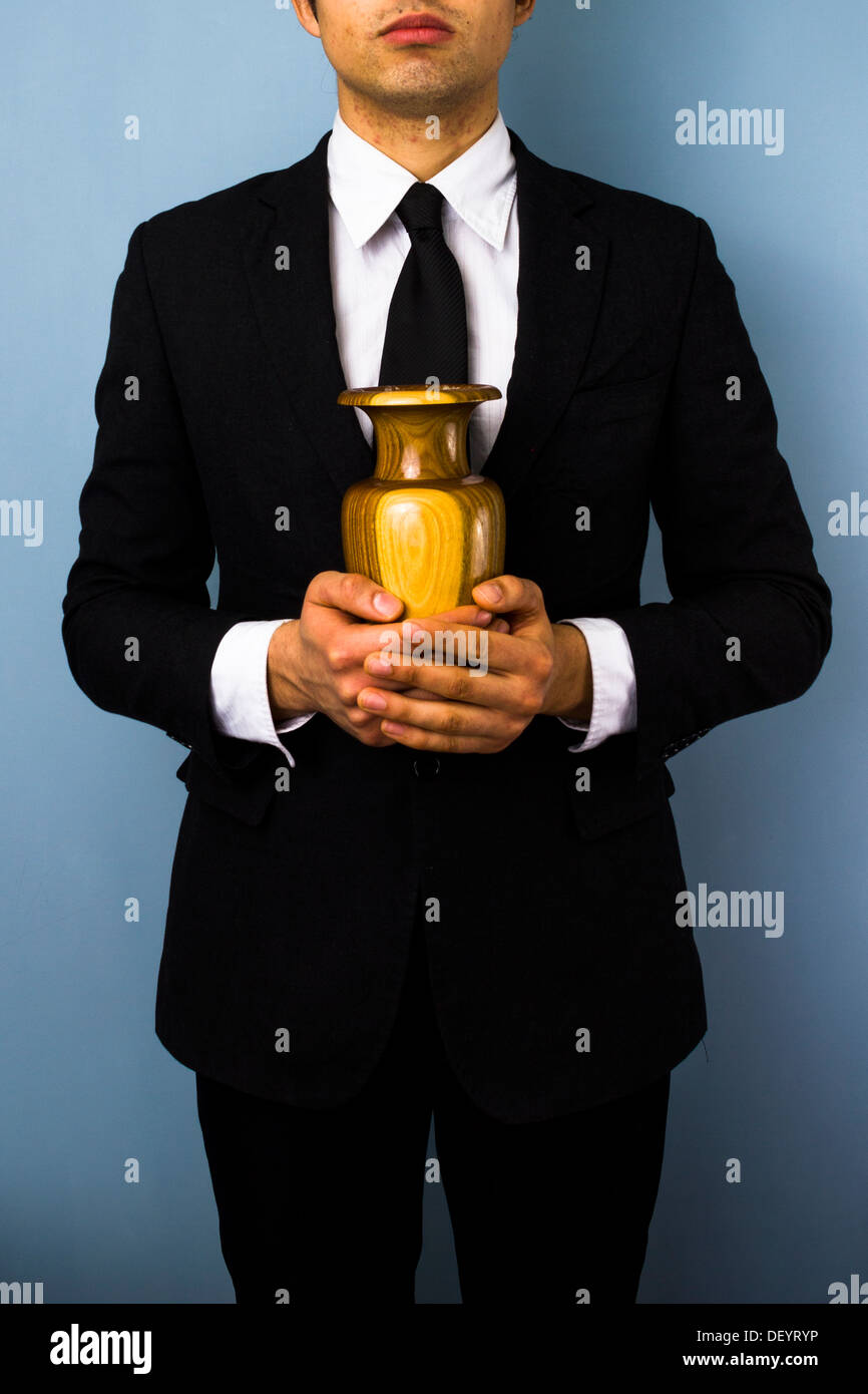 Young man in suit holding a wooden urn - Stock Image