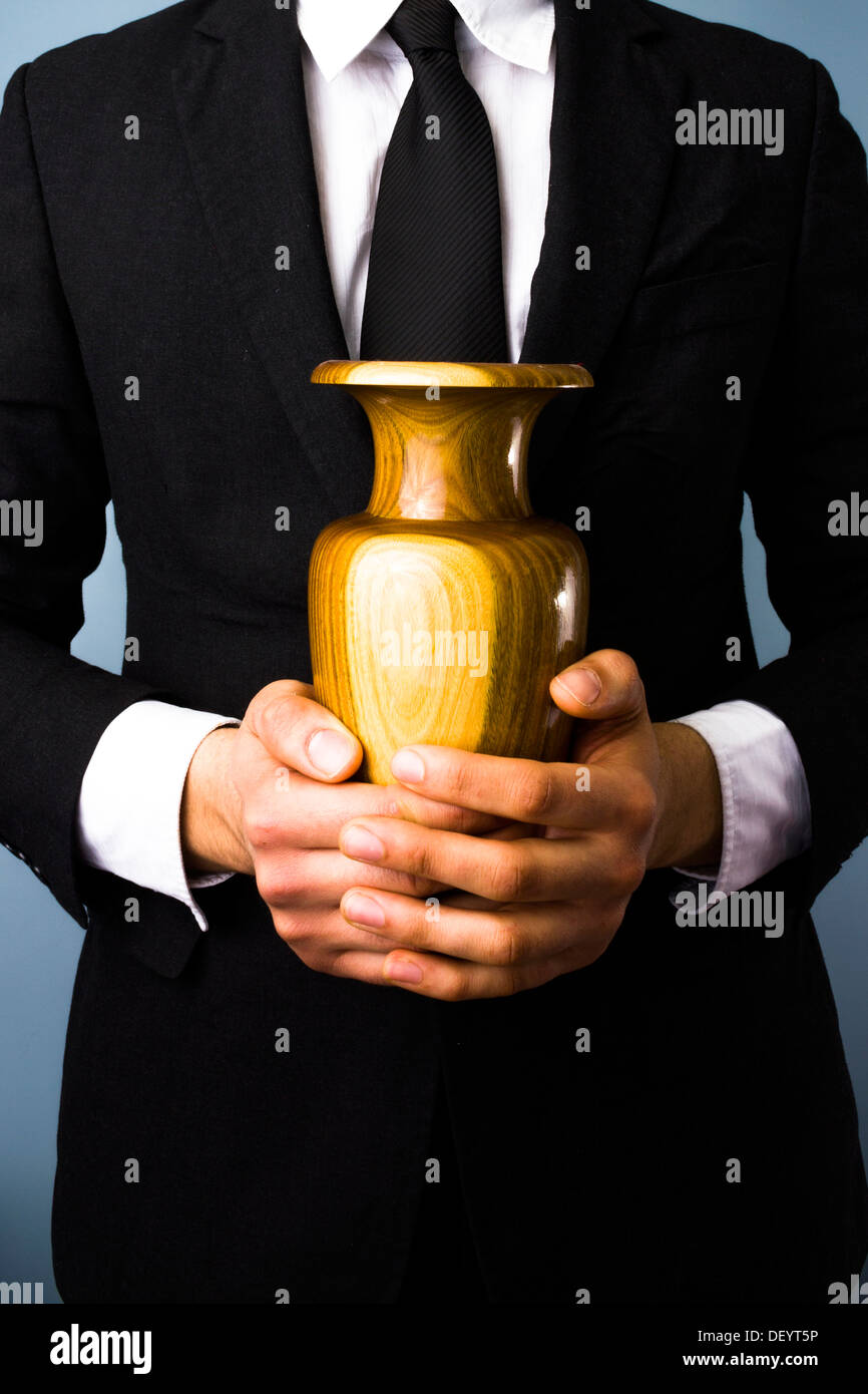Close up of a man in suit holding a wooden urn - Stock Image