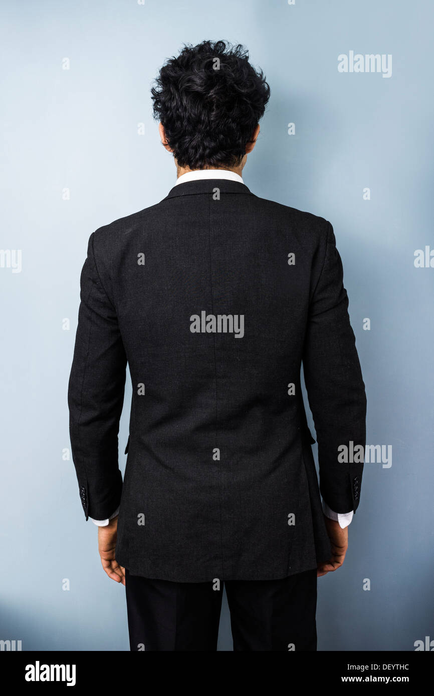 Rear view of young multi racial business man against a blue wall - Stock Image