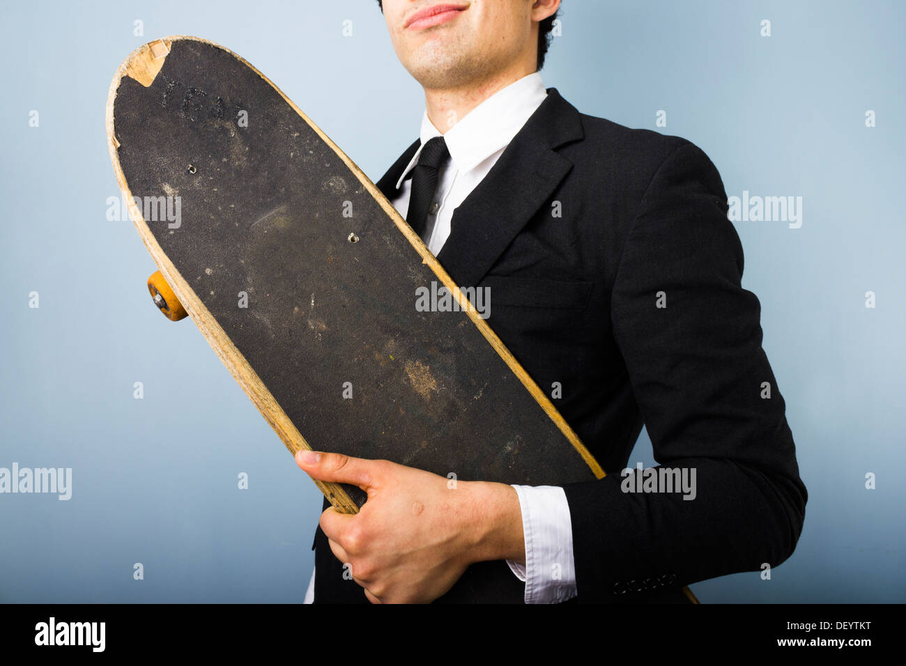 Young businessman looking smug and happy with his skateboard - Stock Image