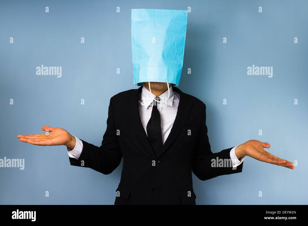 Confused businessman with a paper bag over his head - Stock Image