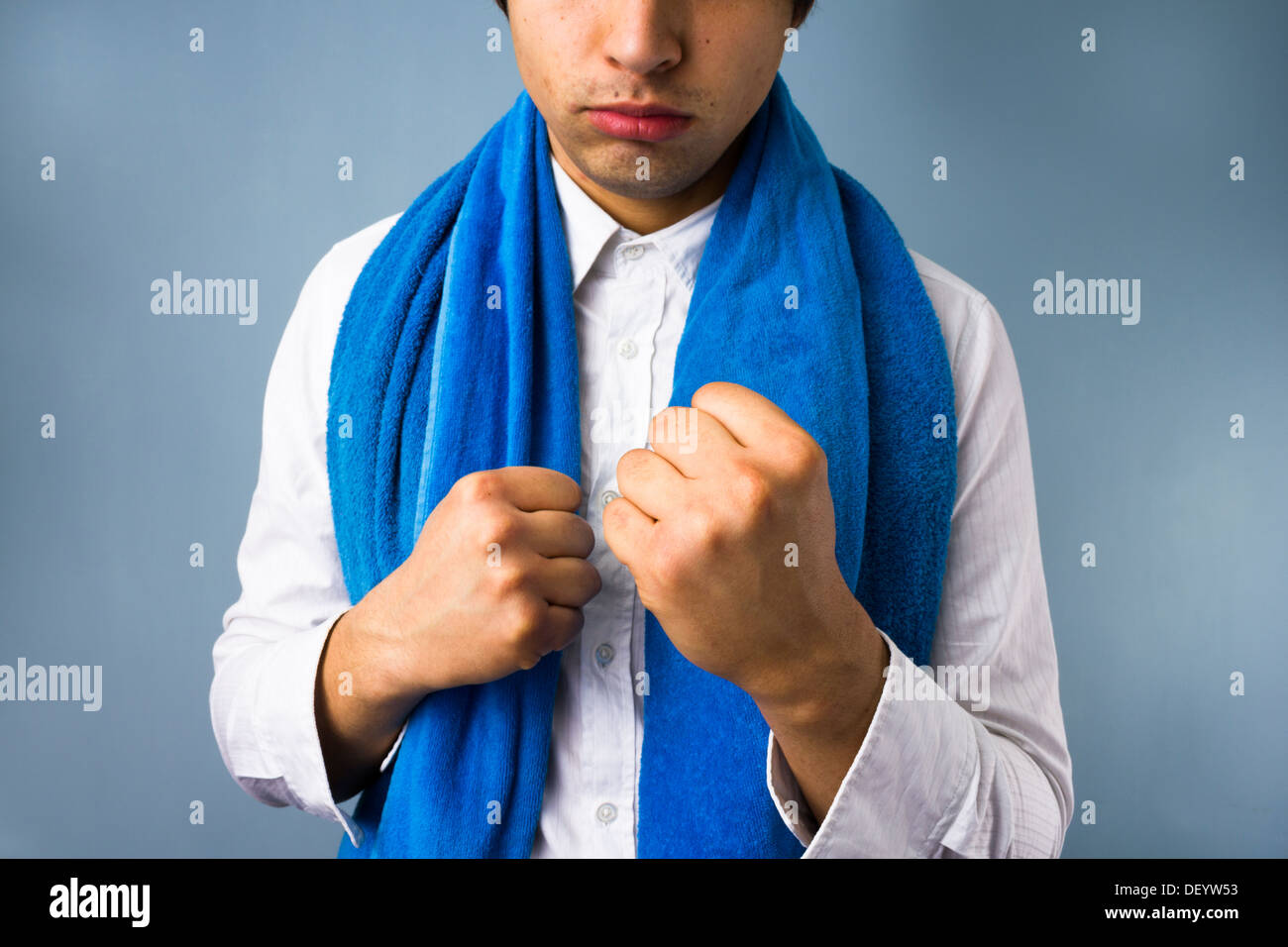 Young businessman and white collar boxer in fighting stance with fists raised - Stock Image