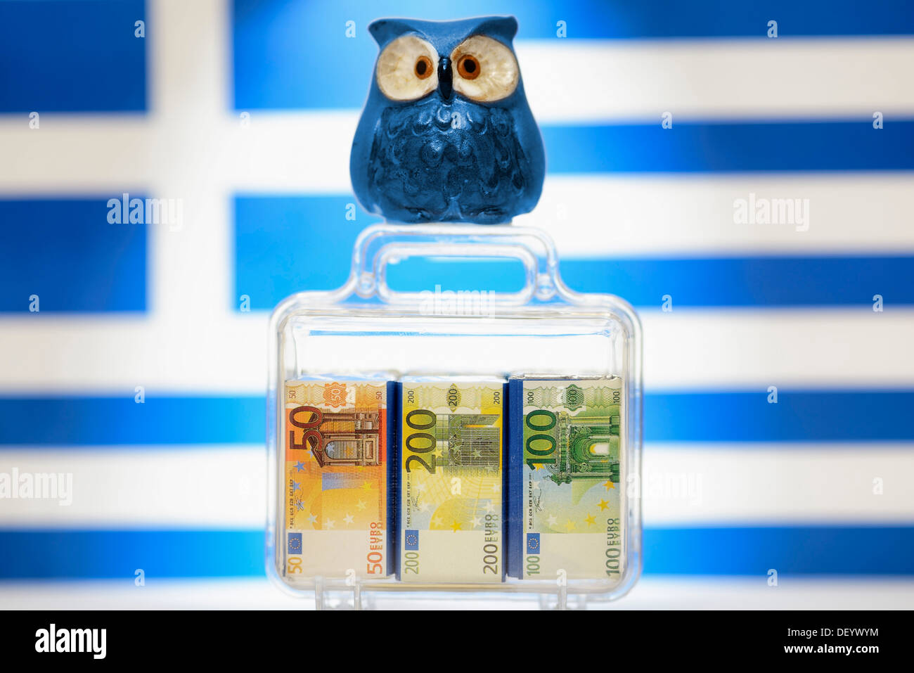 Owl on a suitcase full of money in front of a Greek flag, symbolic image for EU aid to Greece - Stock Image
