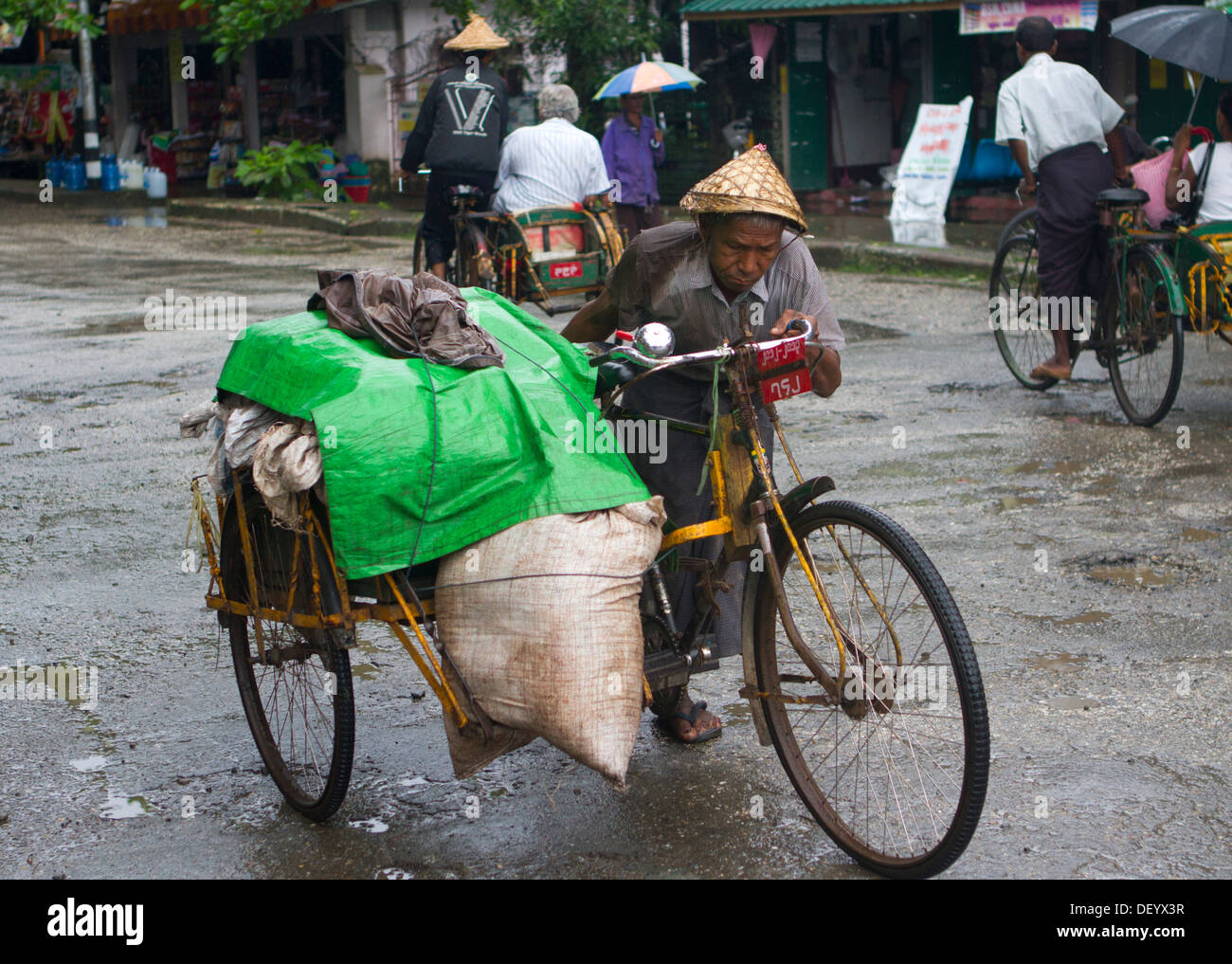 A man pushes his bicycle along the Main Road in Sittwe, Burma. Stock Photo