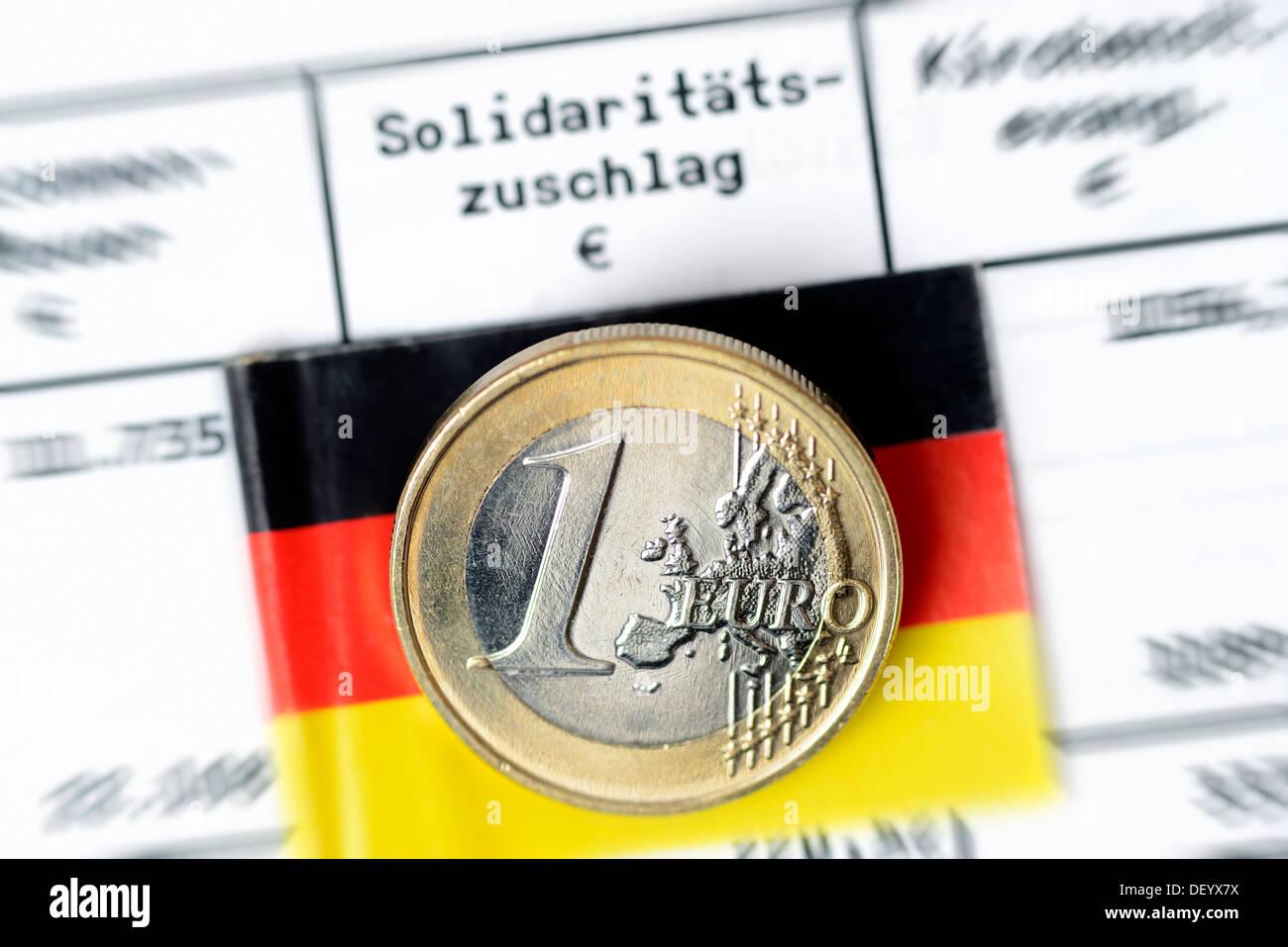 Eurocoin one on income tax answer, retention solidarity tax, Ein-Euro-Münze auf Einkommensteuerbescheid, Beibehaltung Solidaritä - Stock Image