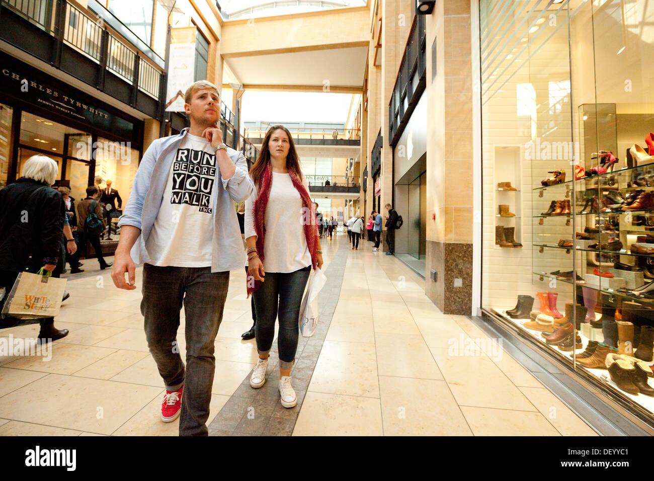 Young couple shopping in a shopping centre center, The Grand arcade shopping Mall, Cambridge England UK - Stock Image