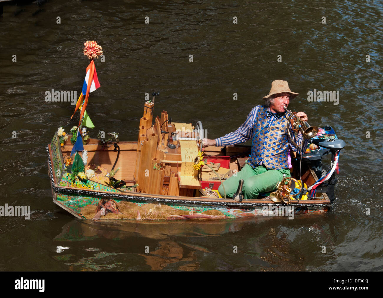 A busker ( Reinier Sijpkens ) playing trumpet in an organ boat on a canal in Amsterdam Netherlands - Stock Image