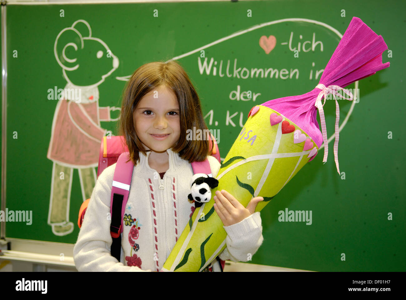 First grader at her first day at school in front of the blackboard - Stock Image