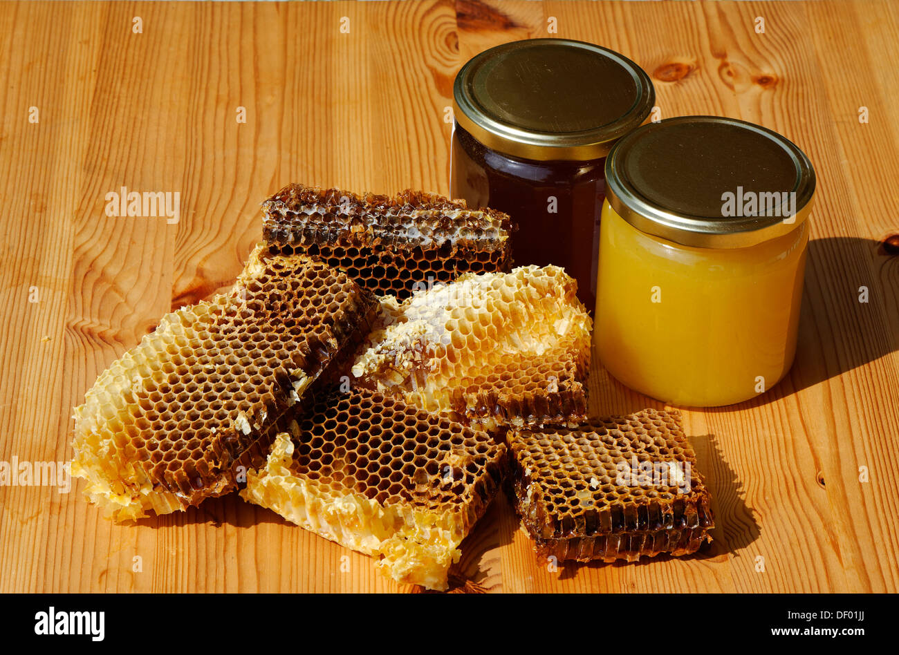 Wild honey and spring honey in jars with honeycombs containing honey - Stock Image