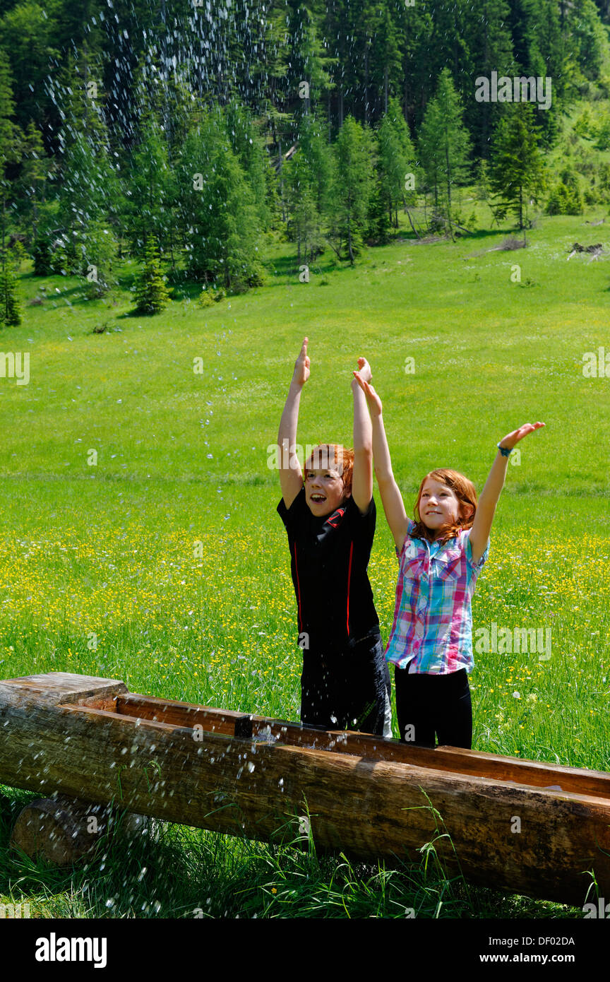 Children splashing water at an animal watering trough, Elendsalm, Klooaschertal valley near Bayerischzell, Blauberge - Stock Image