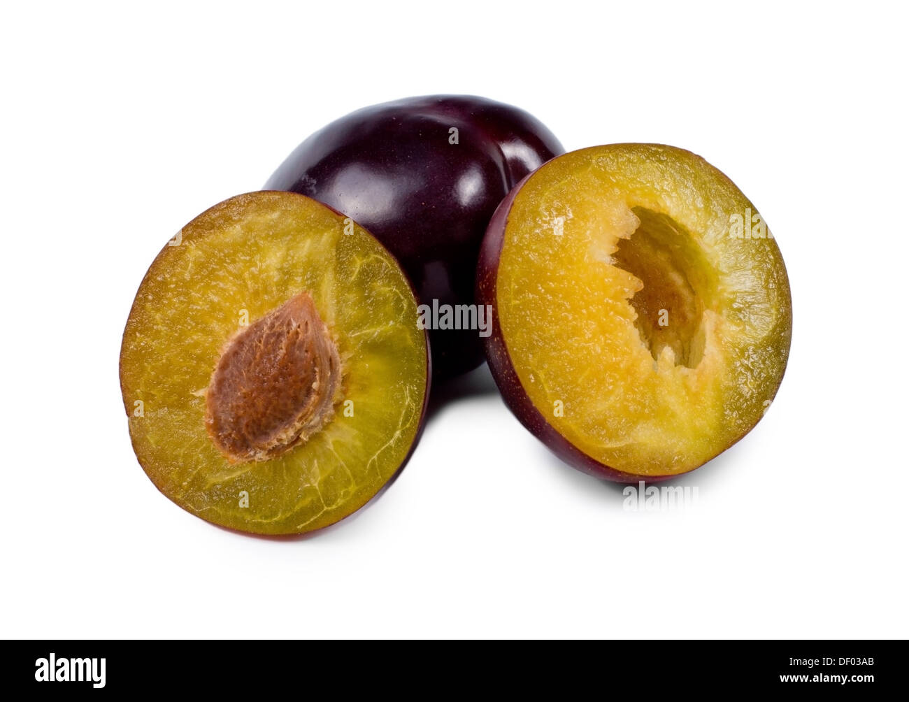Closeup view of the two halves of a fresh purple plum showing the texture of the flesh and pip propped up against Stock Photo
