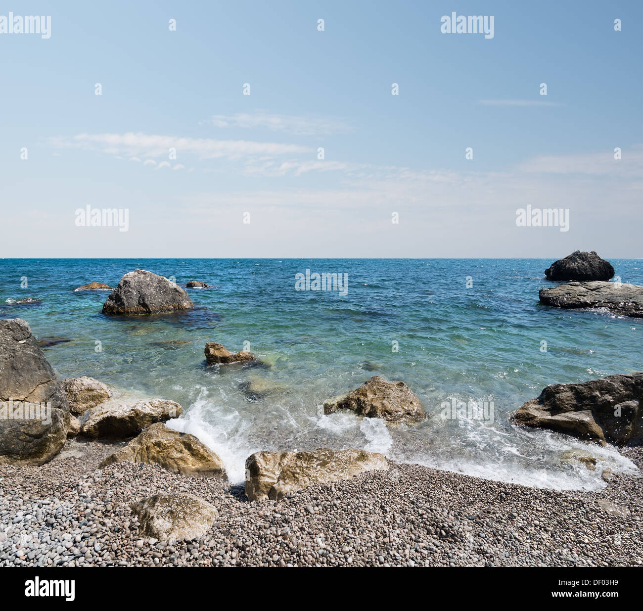 Black sea with stony beach and beautiful clouds - Stock Image