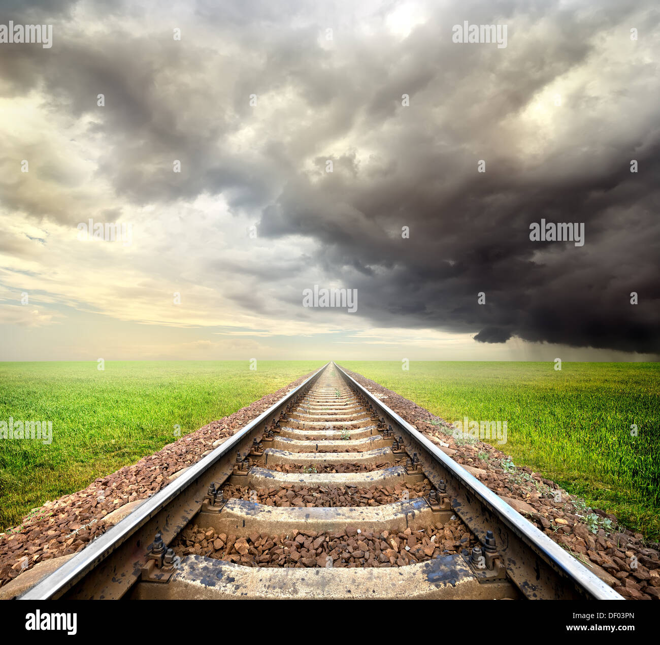 Railway in the field and storm clouds - Stock Image