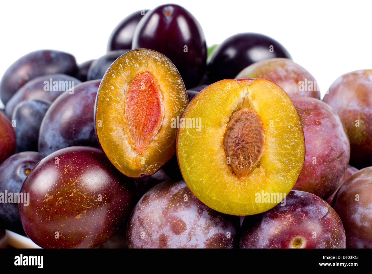 Fresh red plums with one sliced open to reveal the succulent yellow flesh and pip, over white Stock Photo