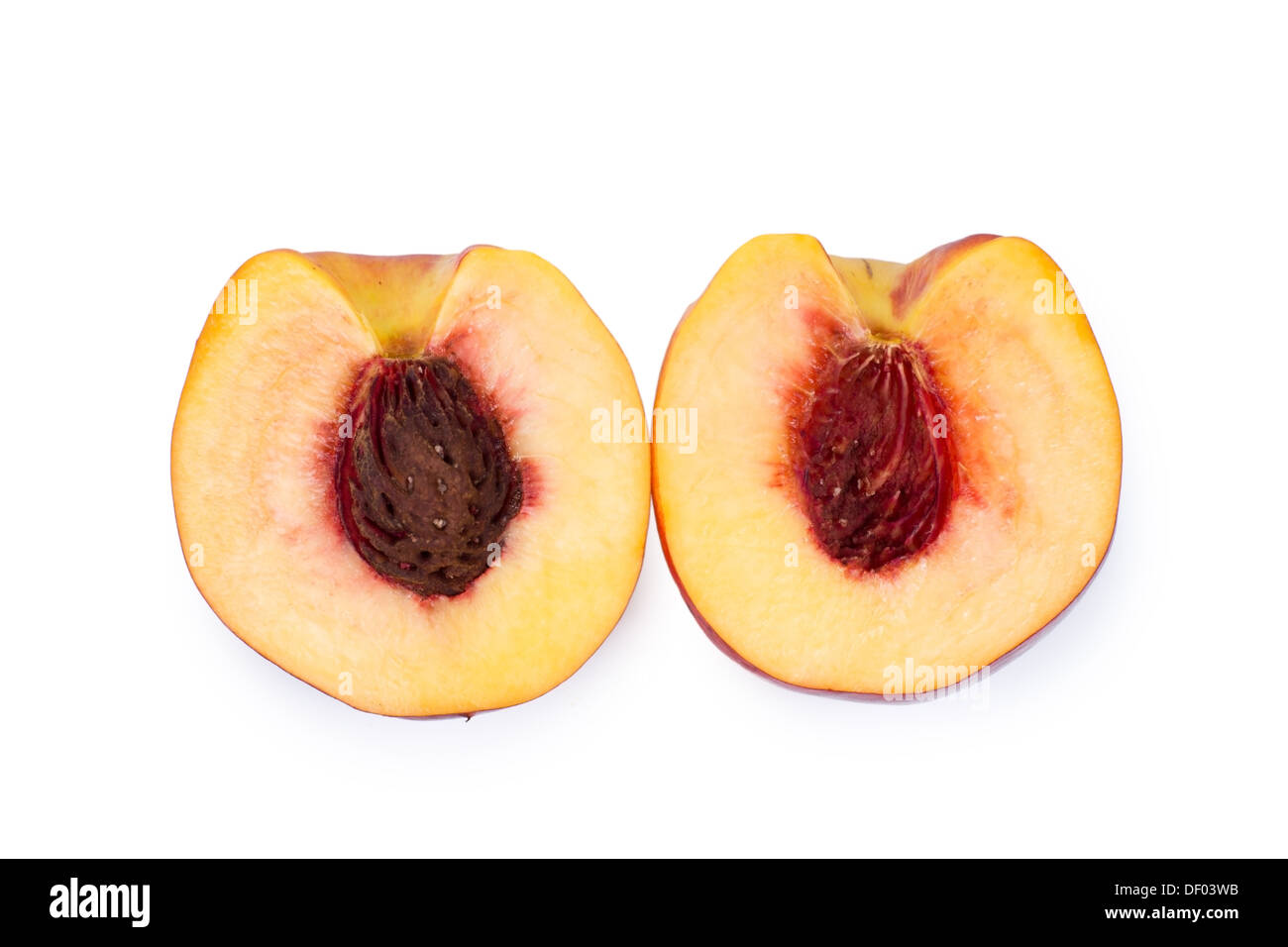 Overhead view of the two halves of a halved juicy ripe nectarine showing the texture of the flesh and pip, isolated Stock Photo