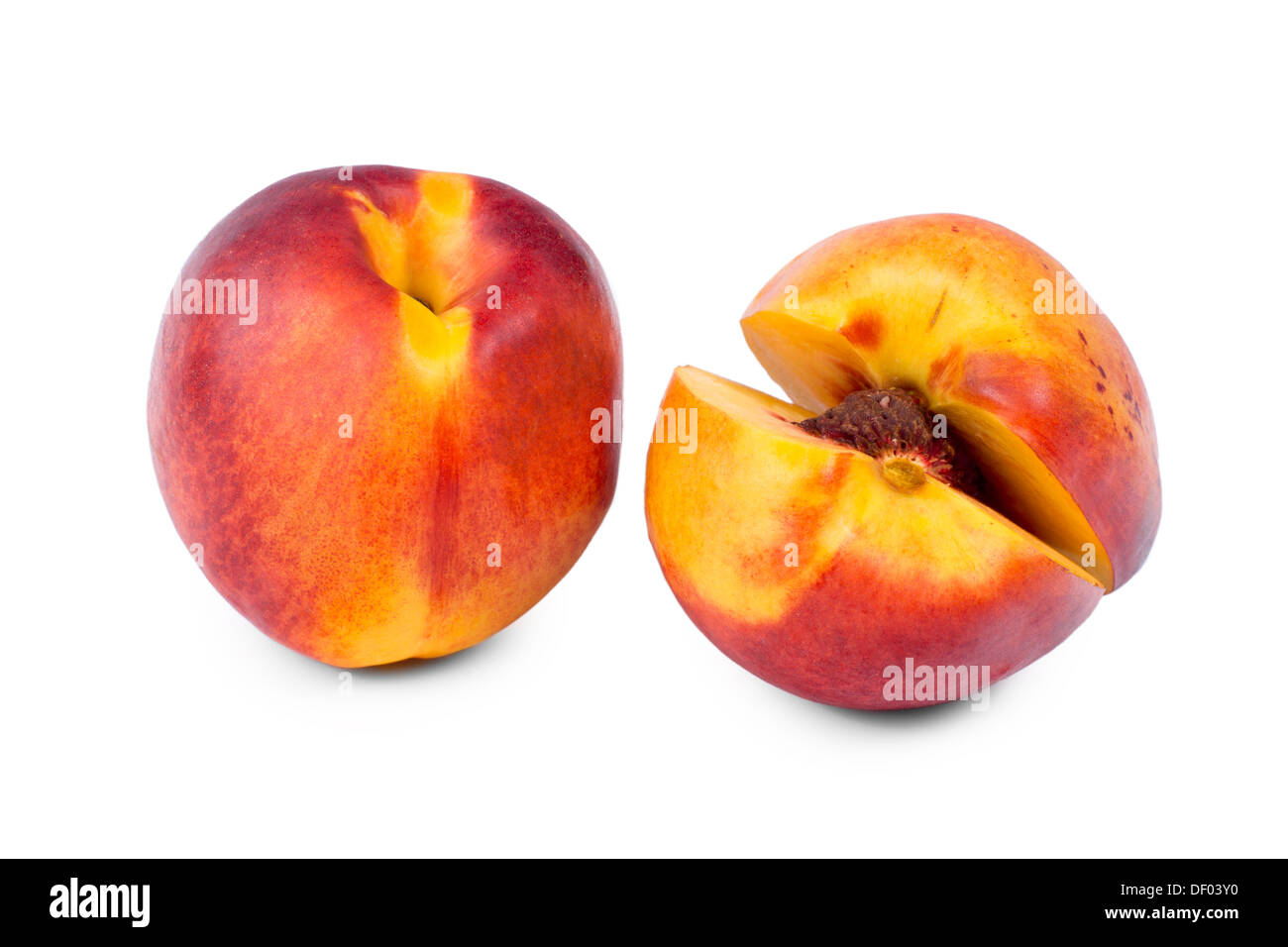Whole and sliced nectarine opened to just reveal the pip inside standing side by side on a white background Stock Photo