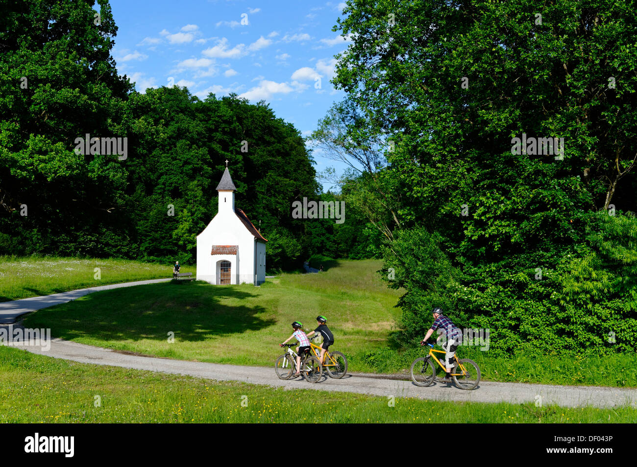 Father and children cycling, mountain biking, Chapel of St. Ulrich, Muehltal valley, Pupplinger Au, near Wolfratshausen - Stock Image