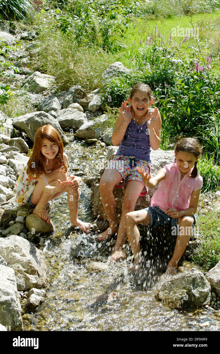 Girls playing and splashing with water, water fight, Kräuter-Erlebnis-Park herb theme park, Bad Heilbrunn, Loisachtal - Stock Image