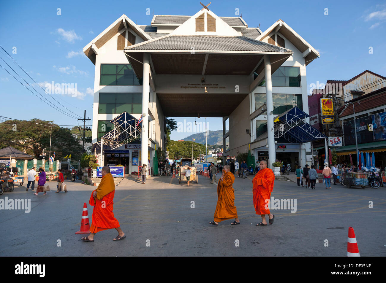Monks walking in front of the border post between Myanmar, Burma, and Mae Sai, Thailand's northernmost town, Northern Thailand - Stock Image