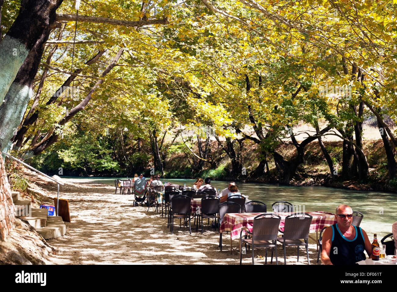 Mainland river diners eating at taverna at riverside under trees Greek Island Greece - Stock Image