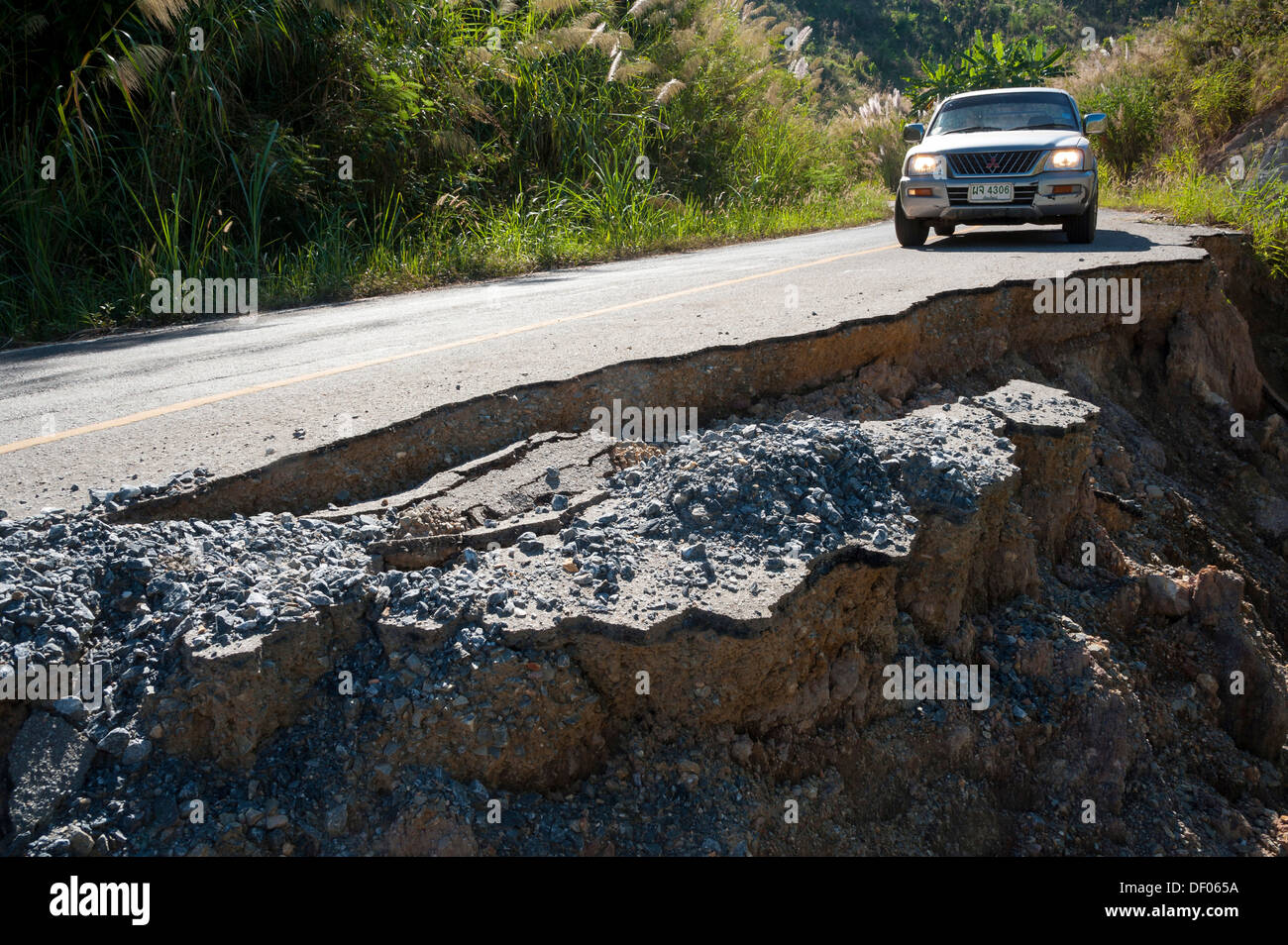 SUV or Pick-up on a destroyed tarmac road, Northern Thailand, Thailand, Asia - Stock Image