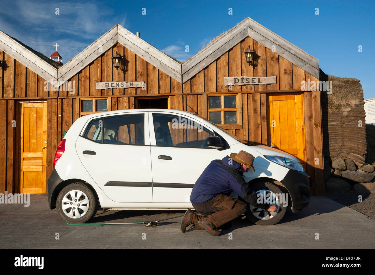 Man kneeling next to a car checking the tyre pressure, petrol station in a wooden hut, Moeðrudalur, Highlands of Iceland - Stock Image