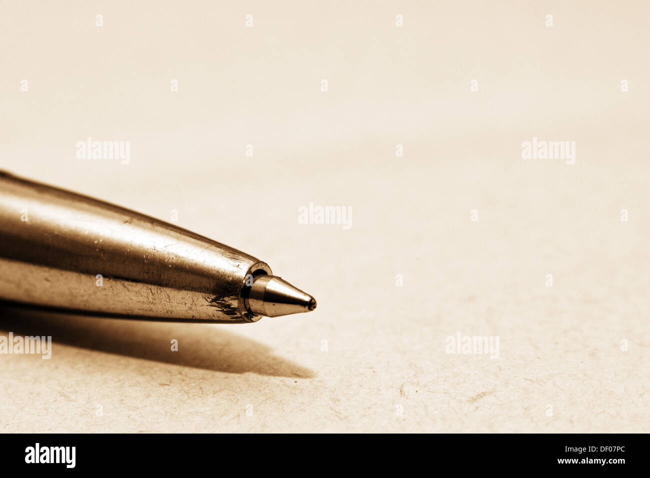 Ballpoint pen tip on yellow paper macro shot Stock Photo