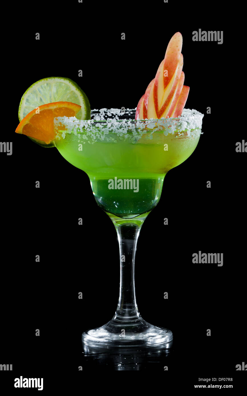 green apple margarita isolated on a black background with an apple garnish - Stock Image