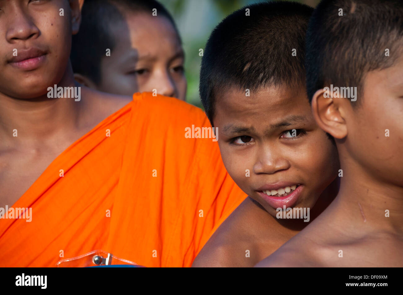 Morning alms round, smiling young Buddhist monk from the monastery school, portrait, Sukhothai Province, Northern Thailand - Stock Image