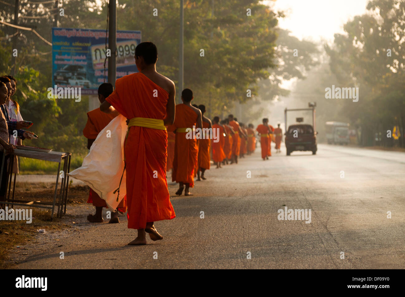 Morning alms round, young Buddhist monks from a monastery school, Sukhothai Province, Northern Thailand, Thailand, Asia - Stock Image