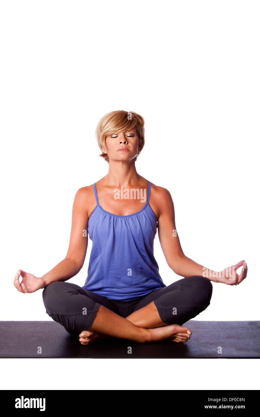 Beautiful woman in Gentle Seated Lotus Position, Padmasana, in yoga meditation to align chakra, on white. - Stock Image