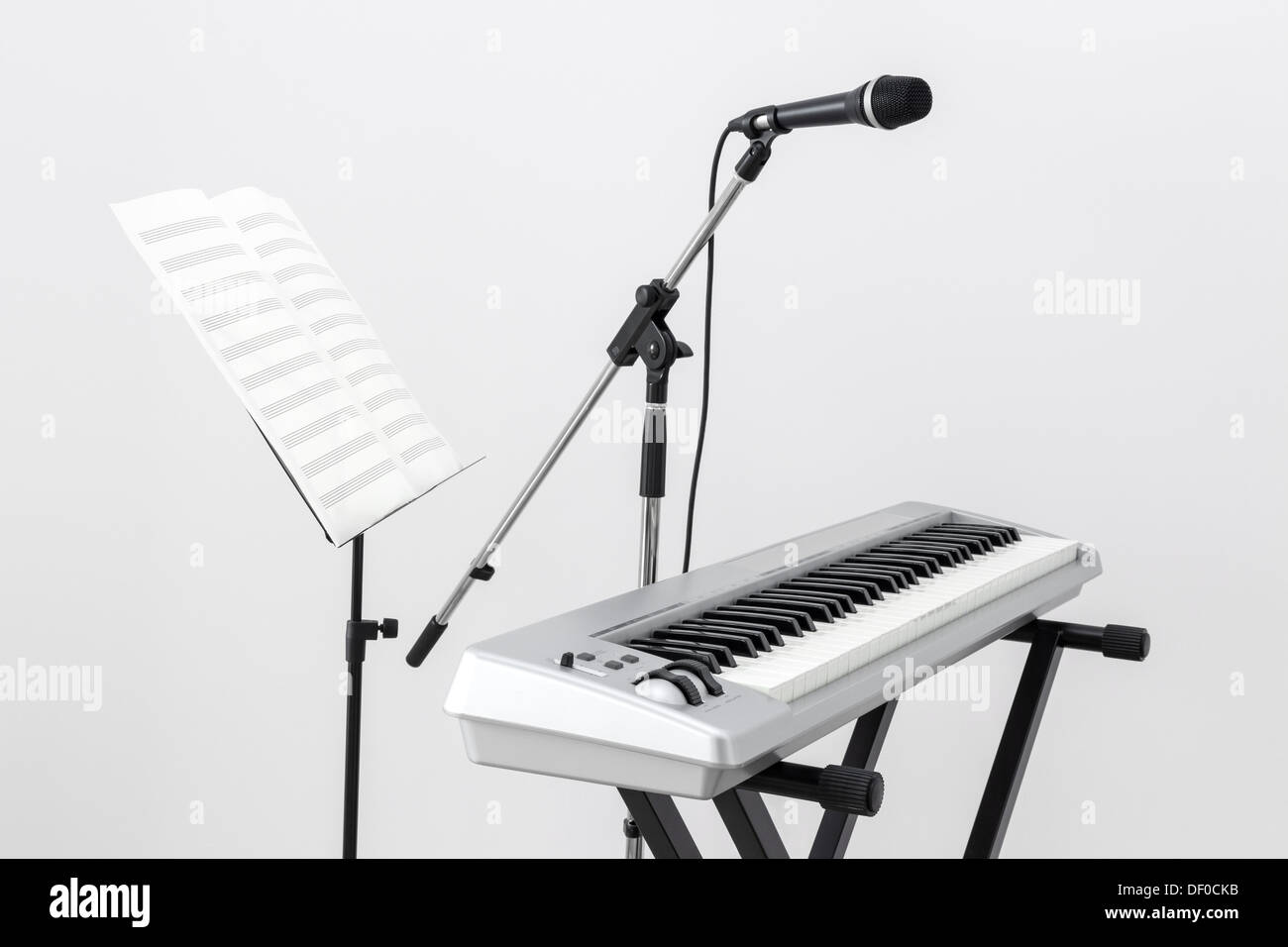 Electric piano, microphone and stand with sheet music. - Stock Image