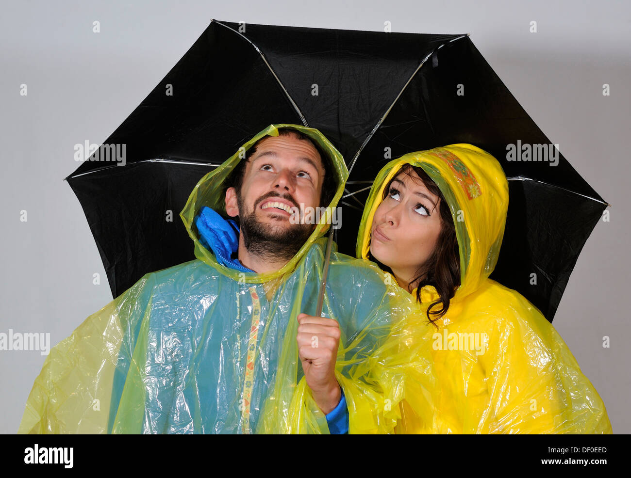 Man and woman standing under an umbrella, symbolic image for weather report - Stock Image