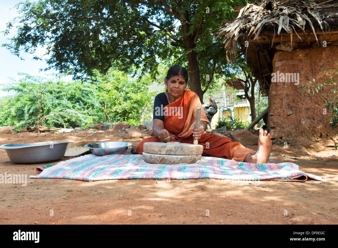 Rural Indian village woman using Quern stones to grind Finger Millet seed / Ragi seeds into Ragi flour. Andhra Pradesh. India - Stock Image