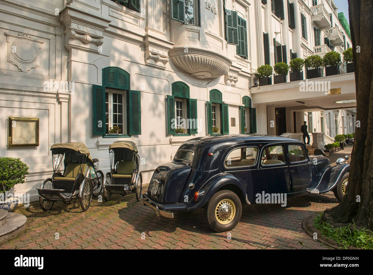 cyclos and vintage car in front of the historic Metropole Hotel in Hanoi, Vietnam - Stock Image