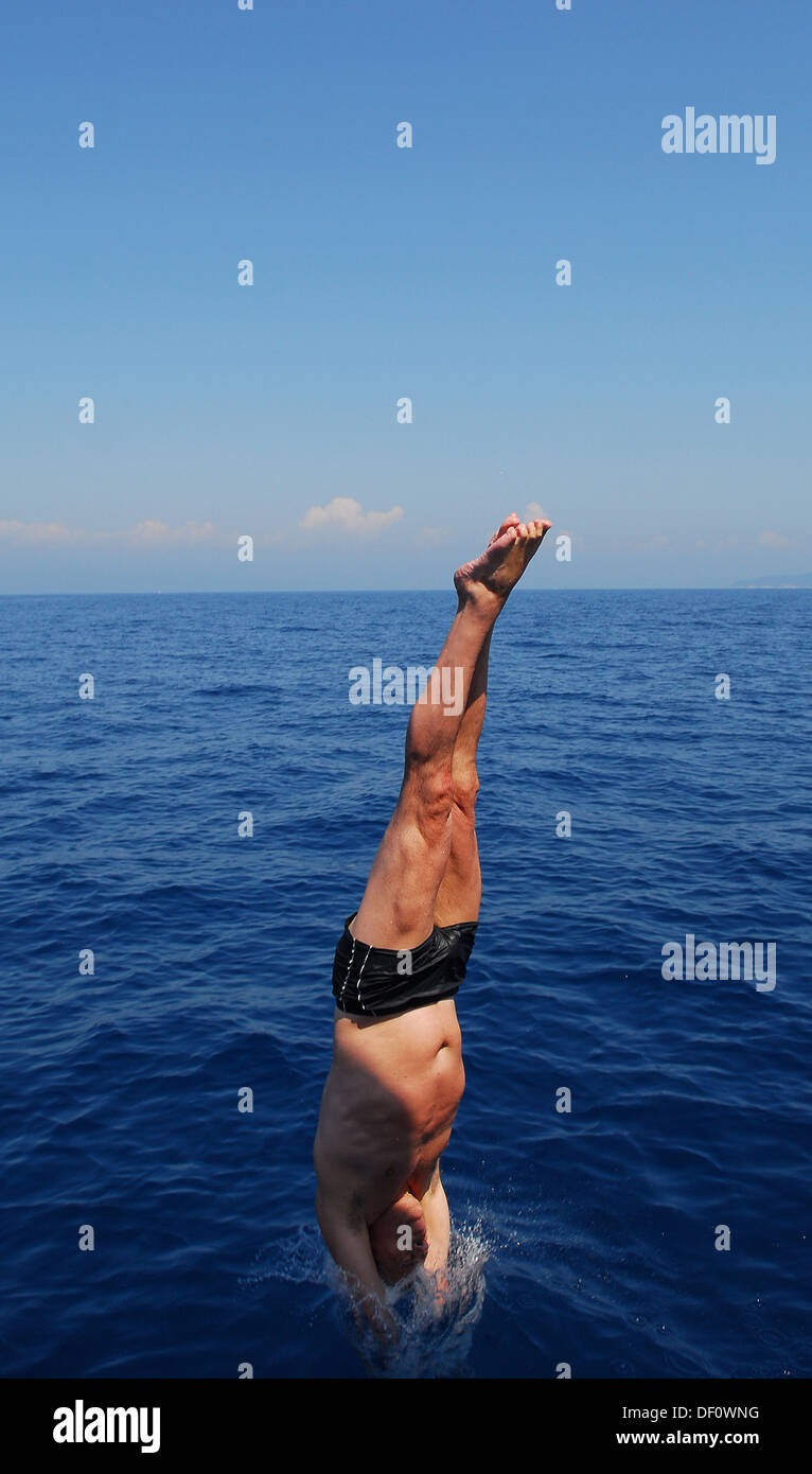 Portoferraio, Italy, a young man jumping head over into the sea, bay Sansone Stock Photo