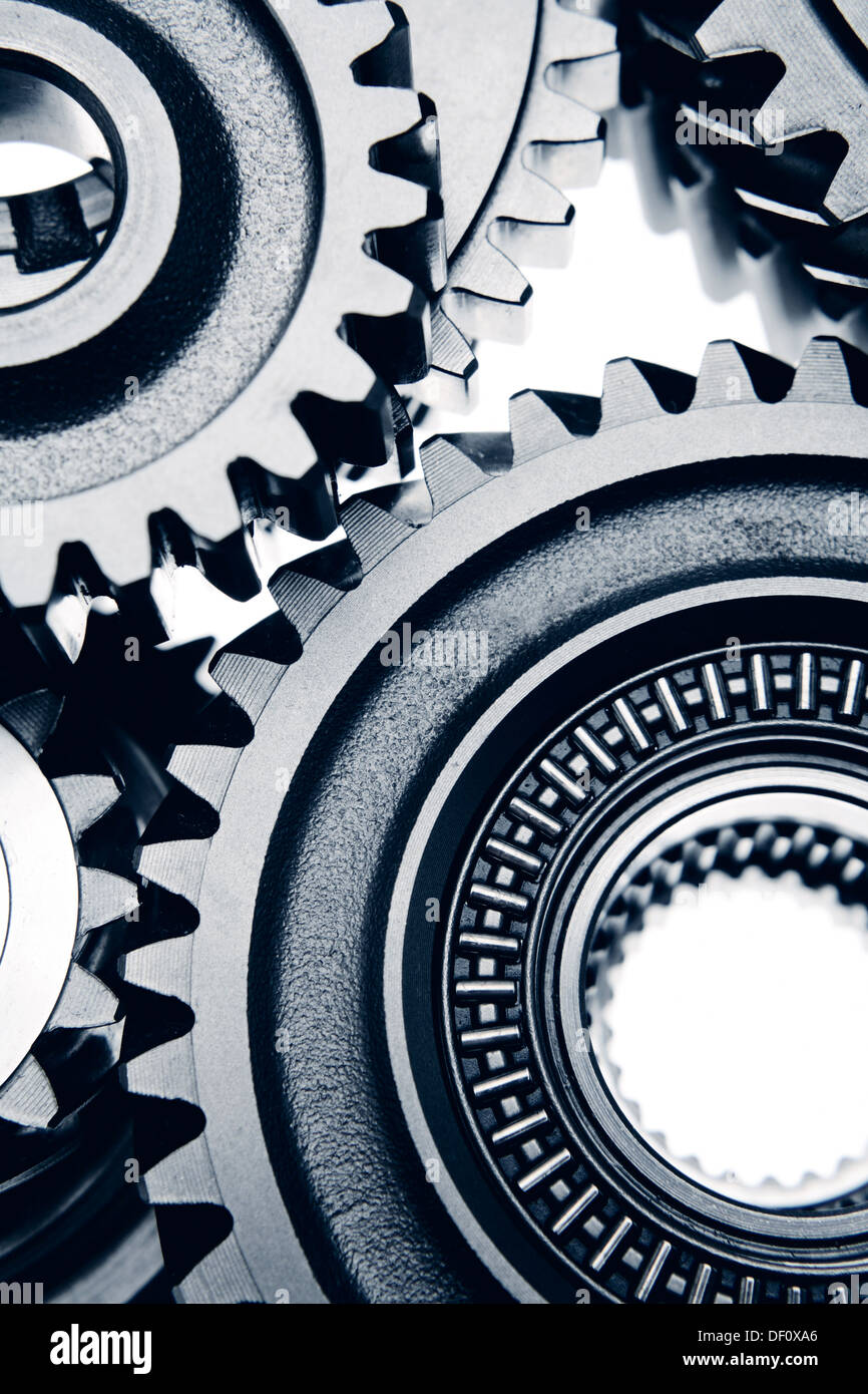 Metal cog wheels bonding together - Stock Image