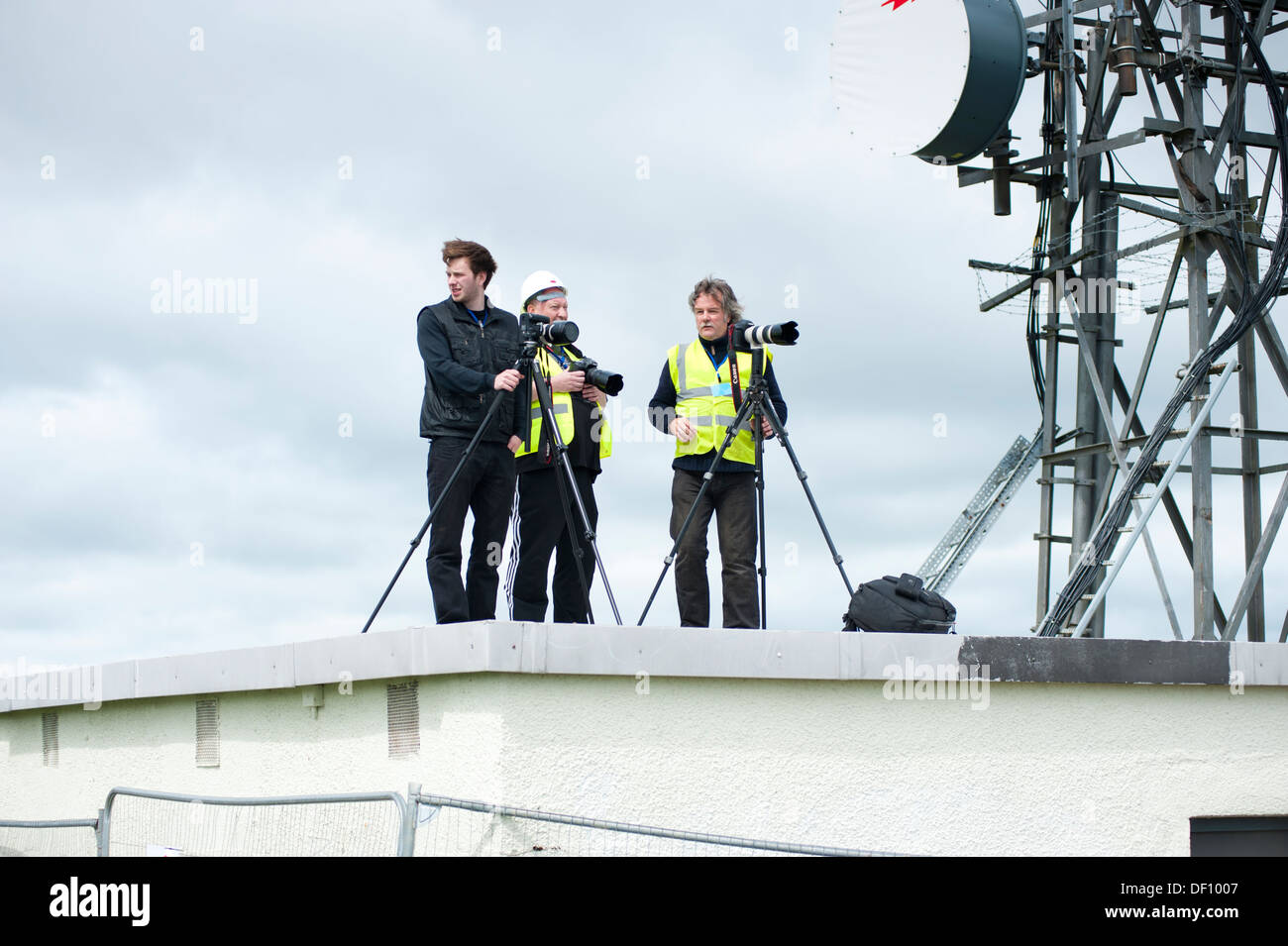 Three photographers on a roof with large antenna telecom mast - Stock Image