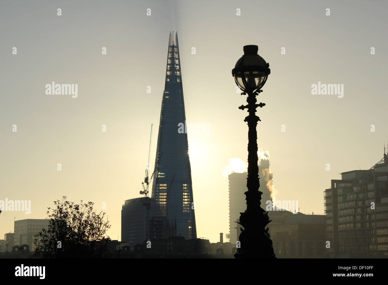 Landscape image of The London Shard and an Old street lamp in the early morning light Steam coming out of buildings behind - Stock Image