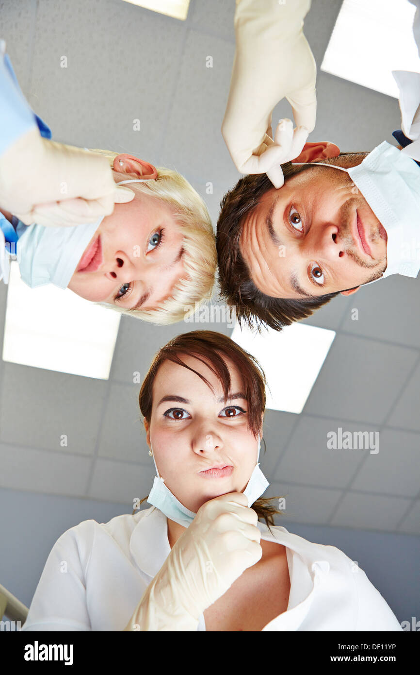 Dentist and dental assistants looking pensive at patient POV - Stock Image