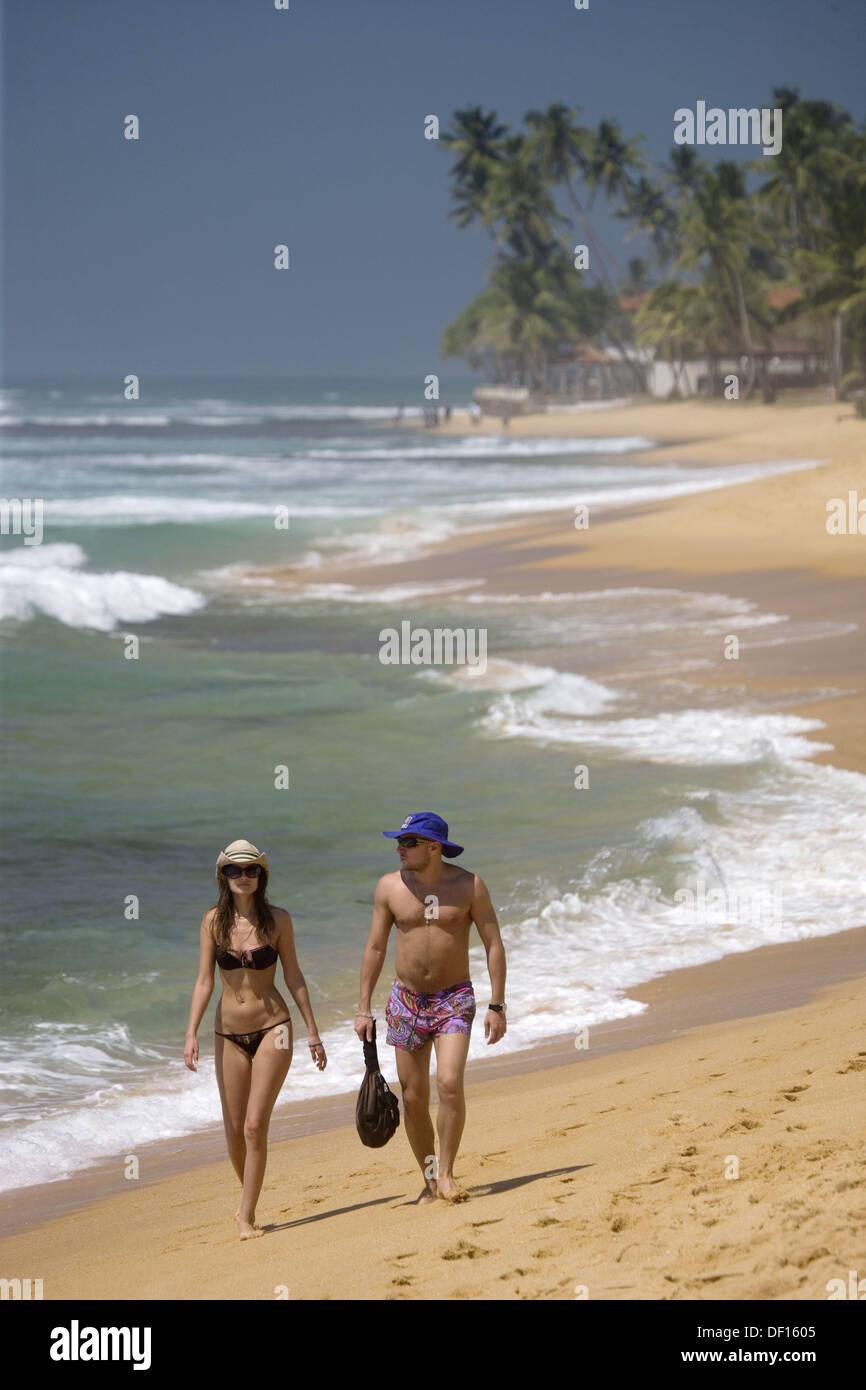 Couple walking along Hikkaduwa Beach, Sri Lanka Stock Photo