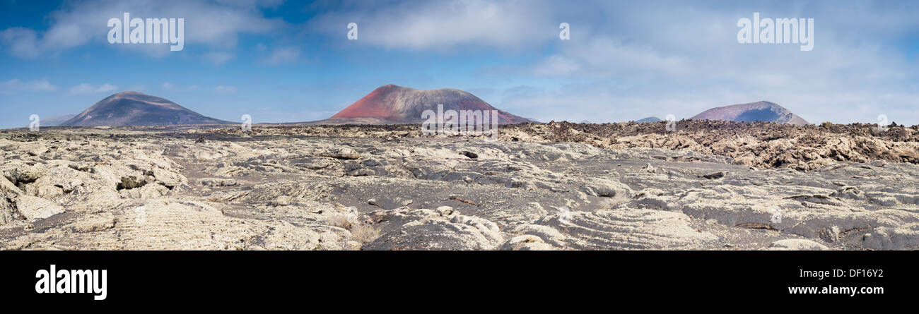 Pahoehoe or ropy lava in foreground, with aa lava right middle and volcanic cones Mons Negra, Colorada and Ortiz in background - Stock Image