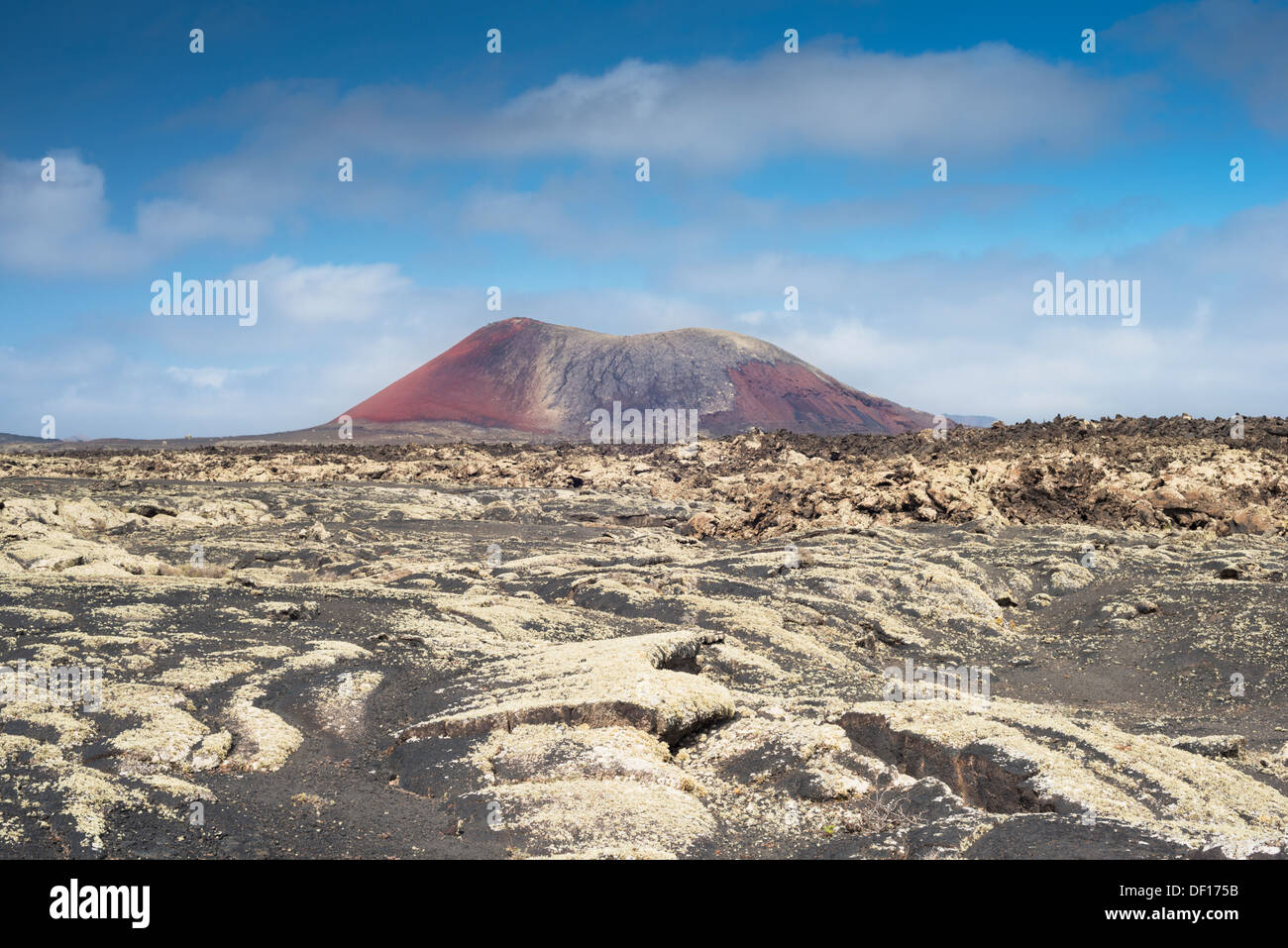 Pahoehoe or ropy lava in foreground, with aa lava middle and the volcanic cone of Montaña Colorada in the background - Stock Image