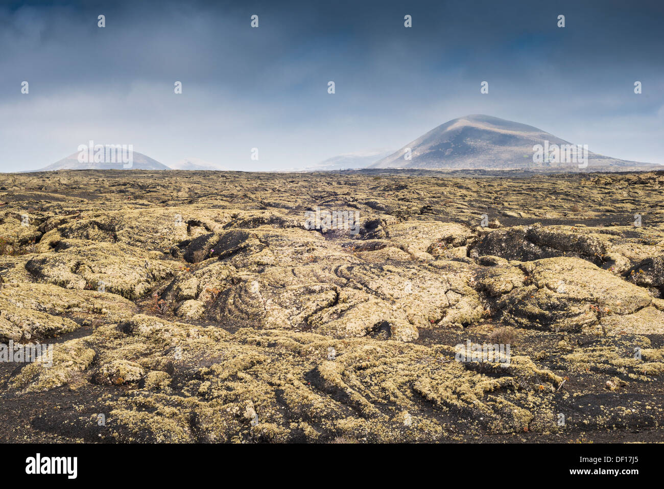 Lichen-covered pahoehoe lava near Masdache, Lanzarote, with Montaña Negra in the distance - Stock Image