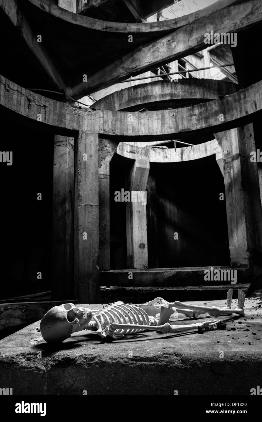 Italy. Site specific. Human skeleton lying in abandoned factory Stock Photo