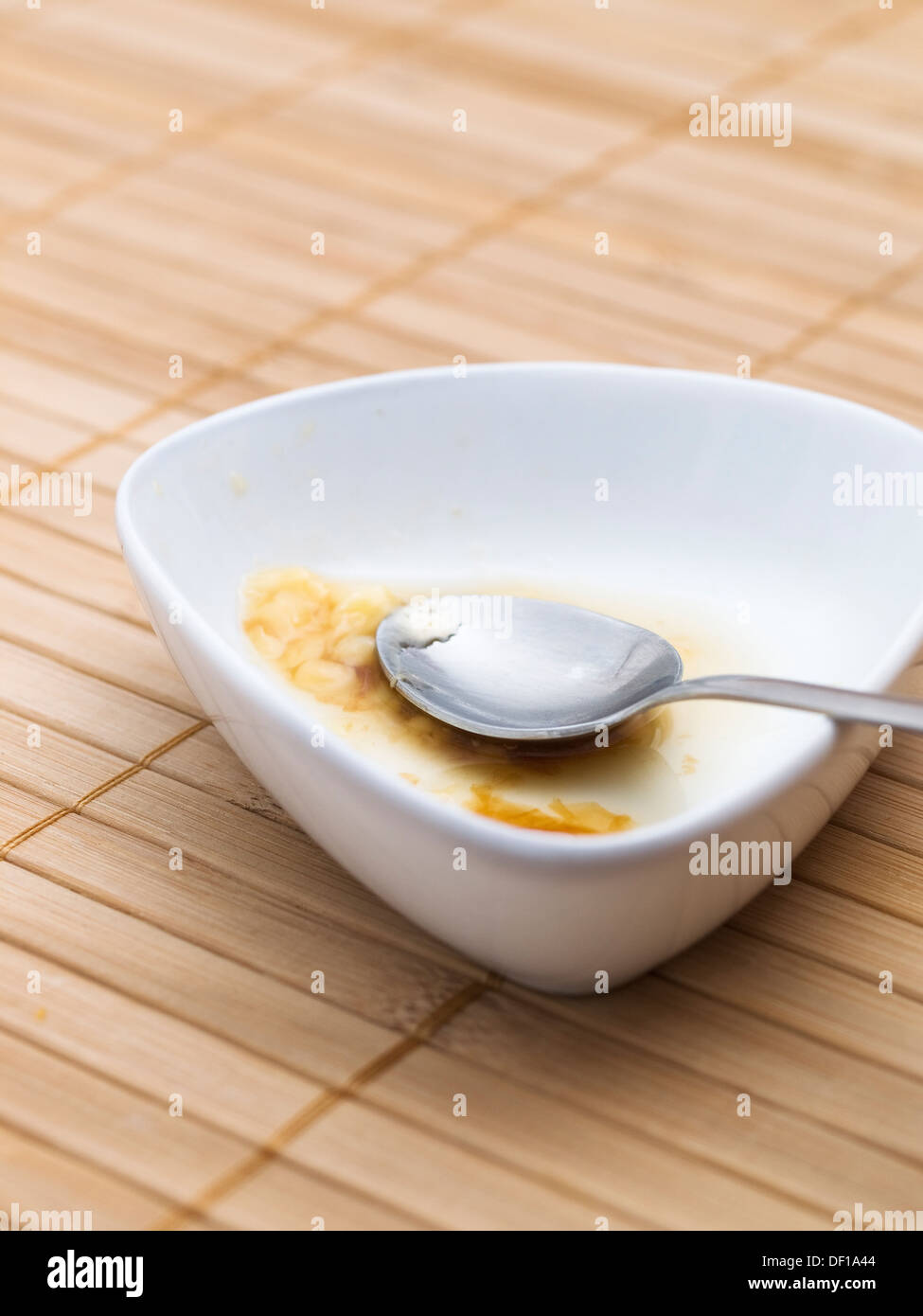 A bowl, a spoon and remains of pudding, macro detail. - Stock Image