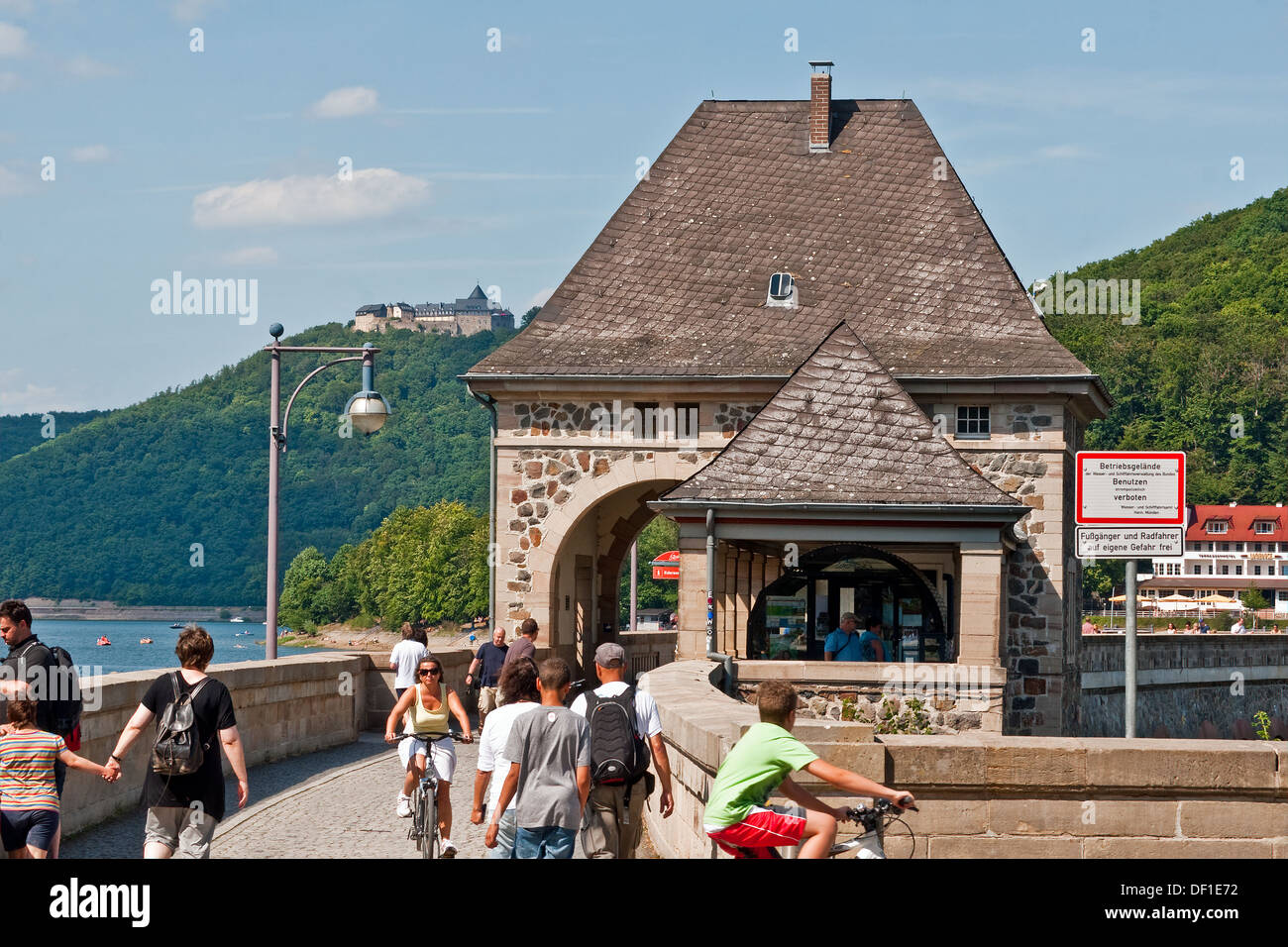 Visitors enjoying summer sunshine on the parapet of the Eder Dam, Germany. Waldeck Castle in the background. - Stock Image